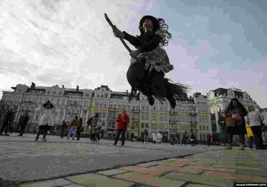 A reveller in costume with a broom jumps during a Zombie Walk event in central Kyiv on October 27, ahead of Halloween celebrations on October 31. (AFP/Anatoliy Stepanov)