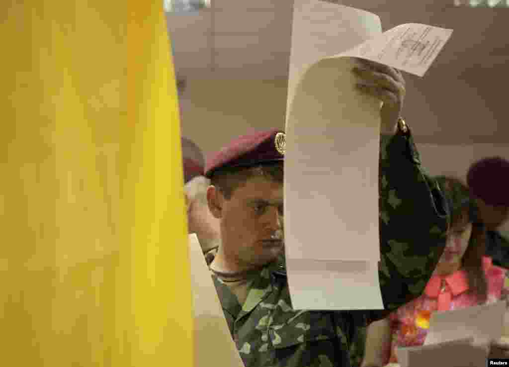 A Ukrainian soldier studies his ballot paper before voting in Kyiv.