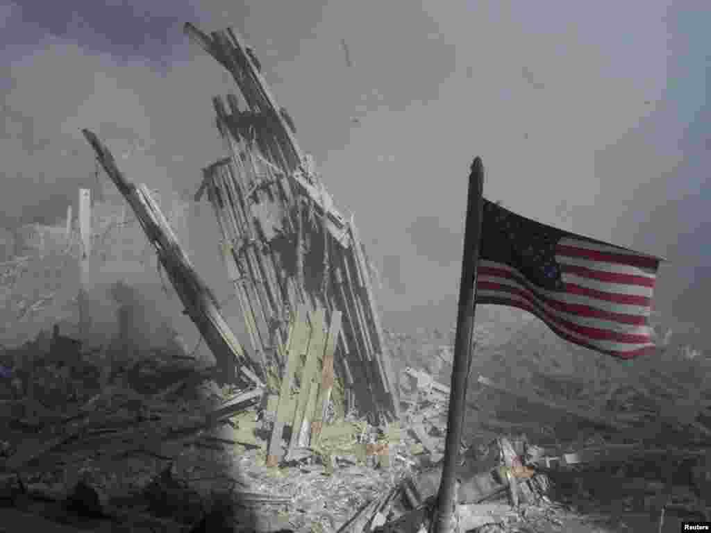 Am American flag flies near the base of the destroyed World Trade Center in New York, September 11, 2001. Planes crashed into each of the two towers, causing them to collapse. REUTERS/Peter Morgan