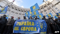 "Protesters hold a sign saying ""Ukraine is Europe"" as they block the Cabinet of the Ministers building in Kyiv on December 2."