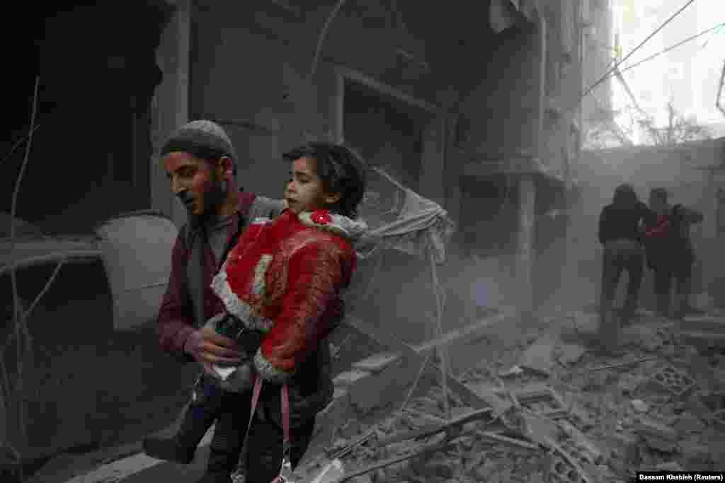 SYRIA -- A man holds a child after an airstrike in the besieged town of Douma, Eastern Ghouta, Damascus, Syria February 7, 2018