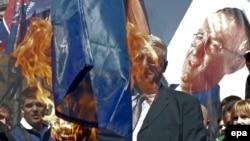 Ваіслаў Шэшаль з прыхільнікамі паляць сьцяг НАТО на мітынгу ў Бялградзе 24 сакавіка