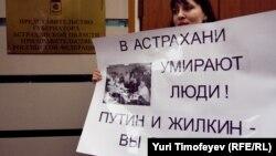 Участница митинга у здания представительства Астраханской области в Москве держит в руках плакат. Москва, 9 апреля 2012 года.