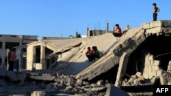 Syrian children slide down the rubble of a destroyed building in the rebel-held city of Daraa on September 12.