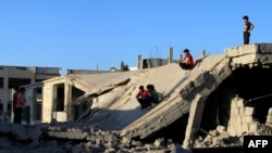 Sirijska djeca izlaze iz srušenih zgrada u provinciji Dera, 12. septembra 2016.