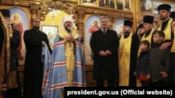 Ukrainian President Petro Poroshenko (center-right) and Metropolitan Epifaniy (center-left), newly elected head of the Orthodox Church of Ukraine, in Dnipro on December 17