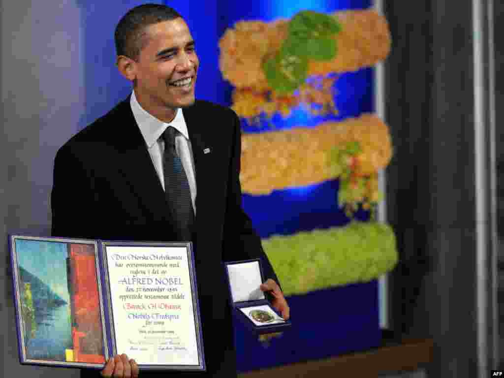 U.S. President Barack Obama poses with his Nobel Peace Prize in Oslo. - As Obama accepted the Nobel Peace Prize on December 10, he faced the difficult task of reconciling the peace award with his decision to send 30,000 troops to escalate the war in Afghanistan. Photo by Jewel Samad for AFP