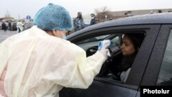 Armenia -- A medical worker checks the temperature of a car driver at a roadblock outside Echmiadzin, March 16, 2020.
