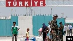 Сирия-Түркия шекарасында бақылау-өткізу бекетінде тұрған әскерилер (Көрнекі сурет).