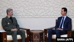 Iranian Defense Minister Amir Hatami (left) meeting with Syrian President Bashar al-Assad in Damascus on August 26.