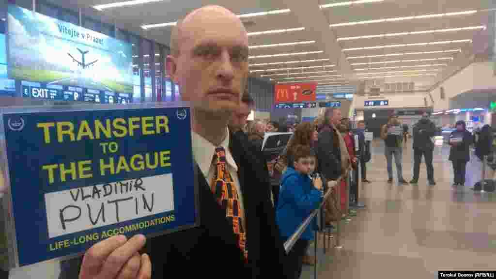 """Активист держит в руках """"документ"""" на """"экстрадицию"""" президента России Владимира Путина в Гаагу, где находится международный трибунал.Прага, 2 апреля 2015 года."""