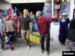 Китаец по имени Миша (в центре) несет вместе с таджикским фермером ящик огурцов. Город Бустонкала, Таджикистан. 14 марта 2011 года.