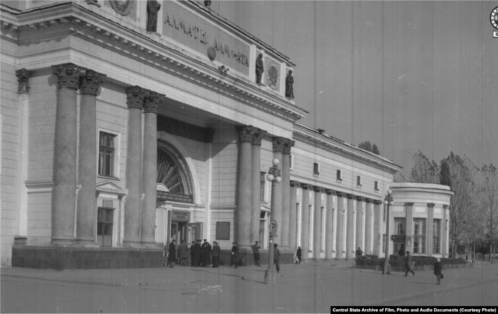 Здание железнодорожного вокзала в городе Алма-Ате. 1950 год (слева).В Верном — так назывался город до 1921 года — в этом районе располагалось кладбище. К моменту строительства вокзала погост был снесен селевым потоком. Здание строилось в 1936–1939 годах архитекторами Галкиным и Кудрявцевым. Пережило реконструкцию в 1977 году и капитальный ремонт в 2012-м. Выходящая к вокзалу улица четыре раза меняла свое наименование: названная Старокладбищенской во времена Верного, в 1933 году она превратилась в проспект Сталина, в 1961 году стала Коммунистическим проспектом, а сейчас называется Абылай-хана.