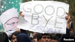 A supporter of Muhammad Tahir-ul-Qadri holds up an antigovernment sign during a fourth day of protests in Islamabad on January 17.
