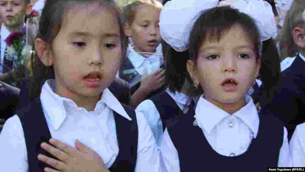 №60 мектеп-гимназиядағы алғашқы қоңырау мерекесі кезінде балалар Қазақстан гимнін айтып тұр.Алматы, 1 қыркүйек 2014 жыл.