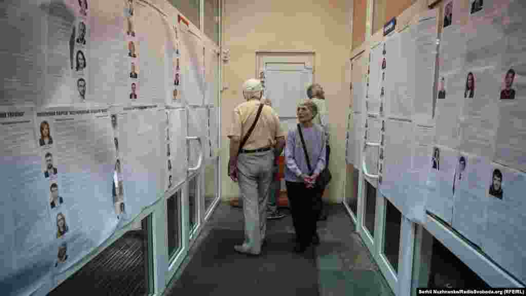 People examine the lists of political parties at a polling station in Kyiv. (RFE/RL/Serhii Nuzhnenko)
