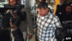 Police escort arrested U.S. national Raymond Davis (center) to a court in Lahore on January 28.