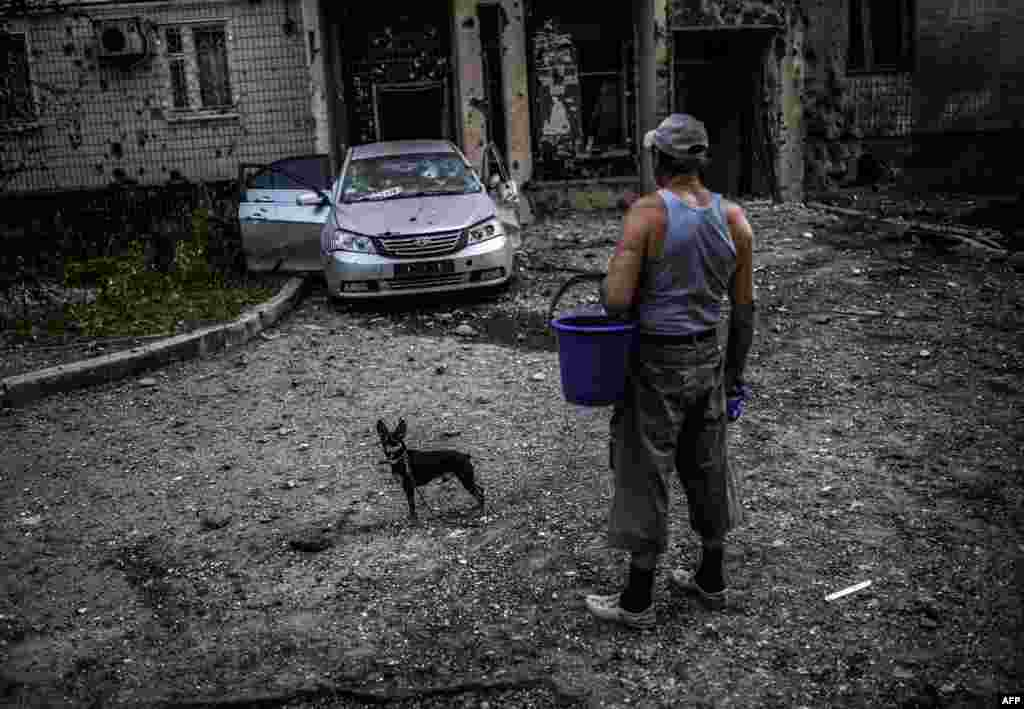 A man with his dog looks at a damaged area after shelling in Donetsk, eastern Ukraine on July 29. (AFP/Bulent Kilic)
