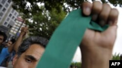 A supporter of Iranian presidential candidate Mir Hossein Musavi waves a green ribbon -- Musavi's campaign color -- during protests in Tehran on June 13.
