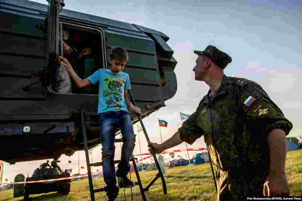 A serviceman helps a child step down after exploring the inside of a military vehicle.