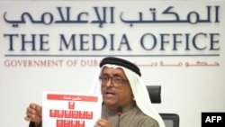 Dubai police chief Dhafi Khalfan holds up identity pictures of 11 suspects in the Hamas commander's killing during a press conference in Dubai on February 15.