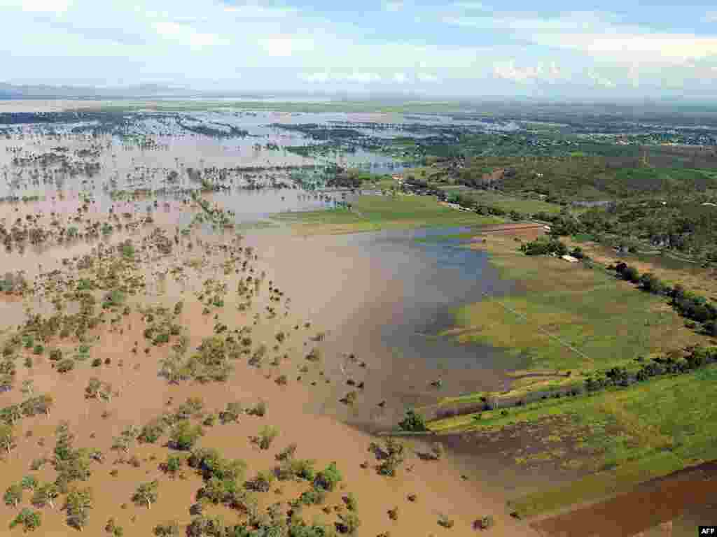 AUSTRALIA, Rockhampton : Rising flood waters inundate fertile farmland near Rockhampton on January 5, 2011 after the swollen Fitzroy River broke its banks. Tens of thousands of people in Rockhampton braced for complete isolation as waters, which have affected an area bigger than France and Germany combined and closed the town's airport and railway, lapped at the last remaining road link. AFP PHOTO / Torsten BLACKWOOD