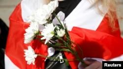 Цветы и бело-красно-белый национальный флаг Беларуси. Участники митинга в поддержку белорусских протестующих. Варшава, 9 сентября