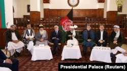 Afghan President Ashraf Ghani flanked by former President Hamid Karzai and other prominent members of Afghanistan's often-divided political elite.