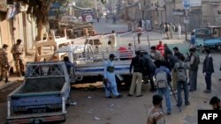 Rangers and policemen inspect a damaged paramilitary van following a bomb blast in Karachi.
