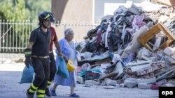 Құтқарушылар зілзала болған аймақта аман қалған егде әйелді алып барады. Лацио, Италия, 29 тамыз 2016 жыл.