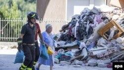 Спасатели ведут пожилую женщину, жительницу региона, где произошло мощное землетрясение. Лацио, 29 августа 2016 года.