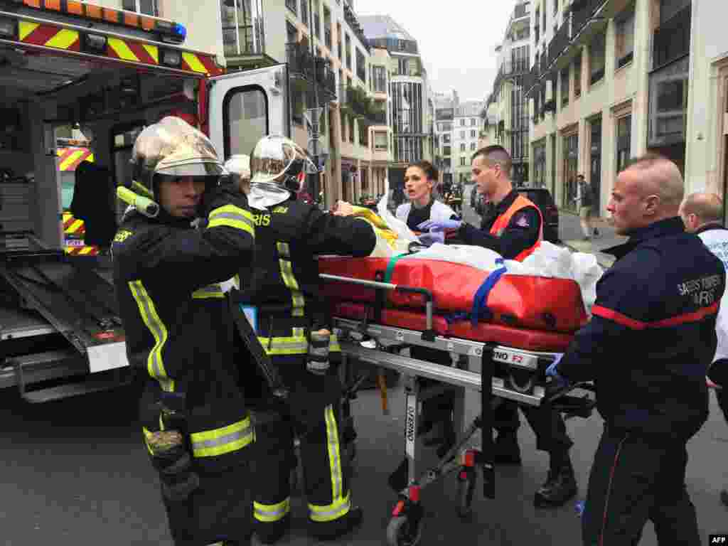 Firefighters carry an injured man on a stretcher in front of the Charlie Hebdo offices.