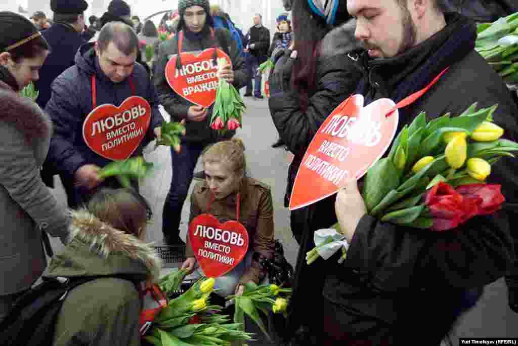 """На нескольких станциях метро активисты с табличками:""""Весна вместо митингов"""", """"Тюльпан вместо Майдана"""", """"Москва цветам поверит"""" и """"Любовь вместо политики"""" встречали пассажиров и дарили им букет тюльпанов."""
