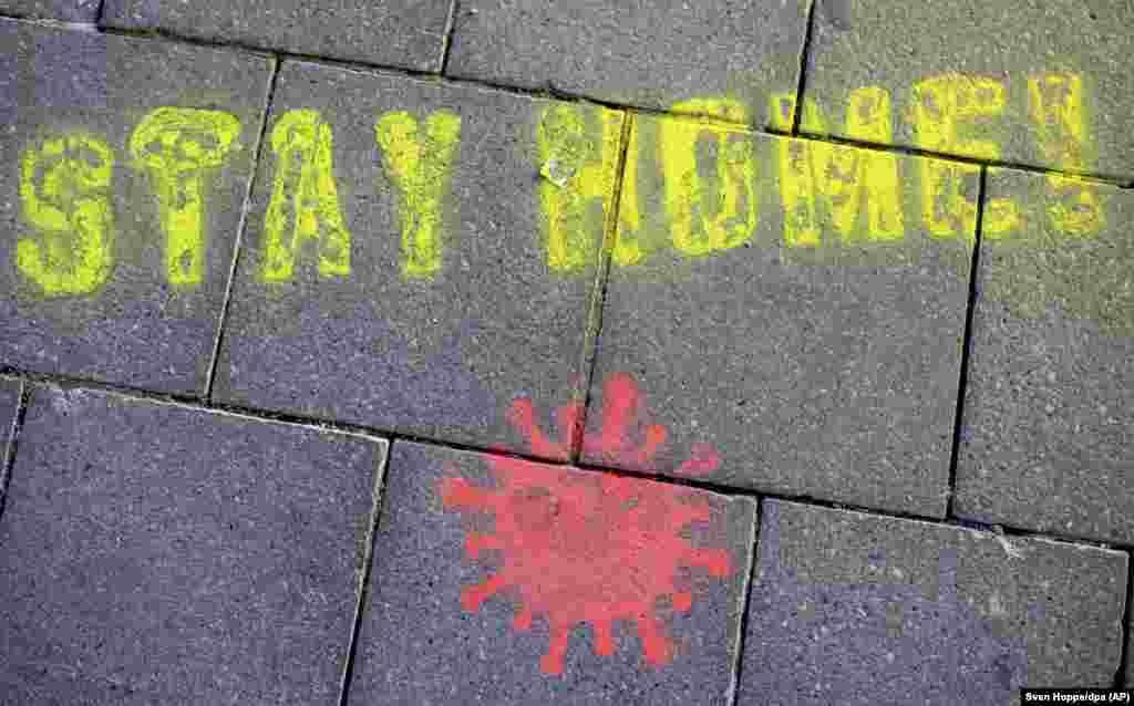 """Графит на тротоар в Мюнхен, който казва на пешеходците """"останете вкъщи""""."""