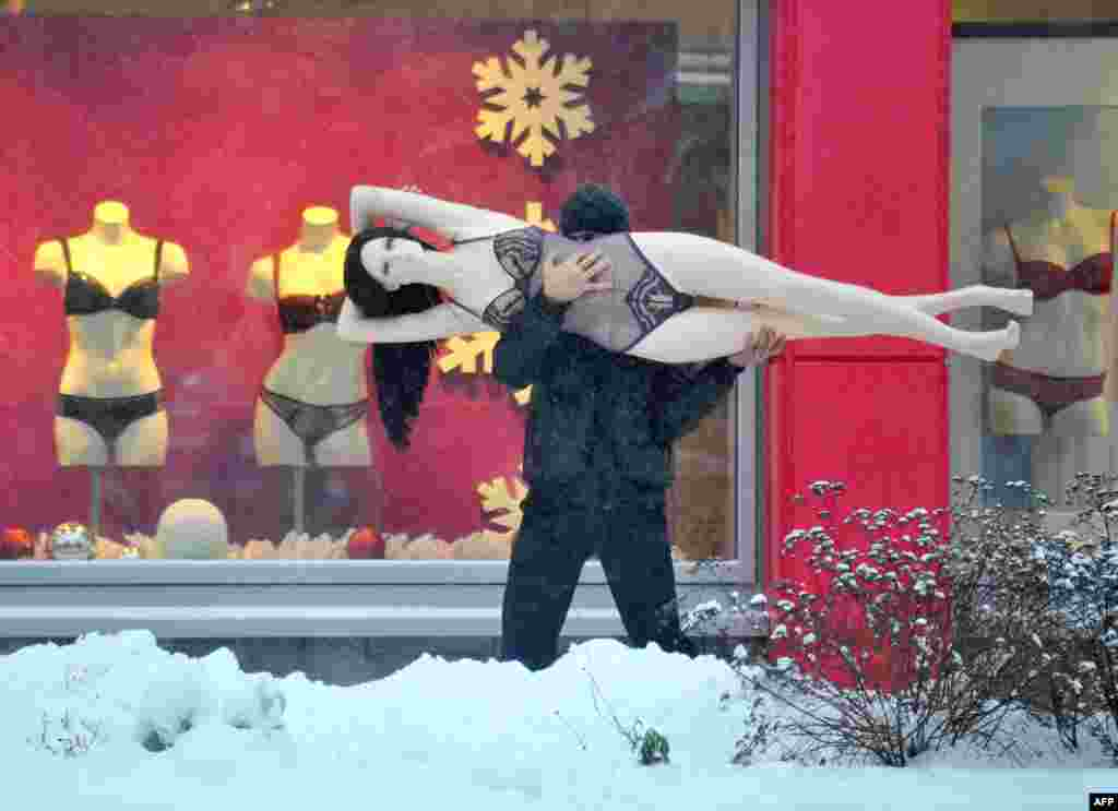 A man carries a mannequin down a snowy street in the Belarusian capital, Minsk. (AFP/Viktor Drachev)