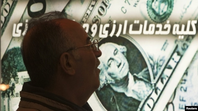 An Iranian man walks past a currency-exchange shop in northern Tehran. Sanctions on Iran have caused the rial to plunge in value, driving up the cost of imports.