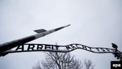 """Главные ворота концлагеря Аушвиц с нацистским лозунгом """"Работа делает свободным"""""""