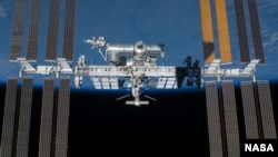 Space -- Backdropped by Earth's horizon and the blackness of space, the International Space Station is featured in this image photographed by an STS-134 crew member on the space shuttle Endeavour after the station and shuttle began their post-undocking re