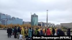 Борышкерлер Бәйтеректен министрлер үйіне бара жатыр. Астана, 1 қазан 2013 жыл.
