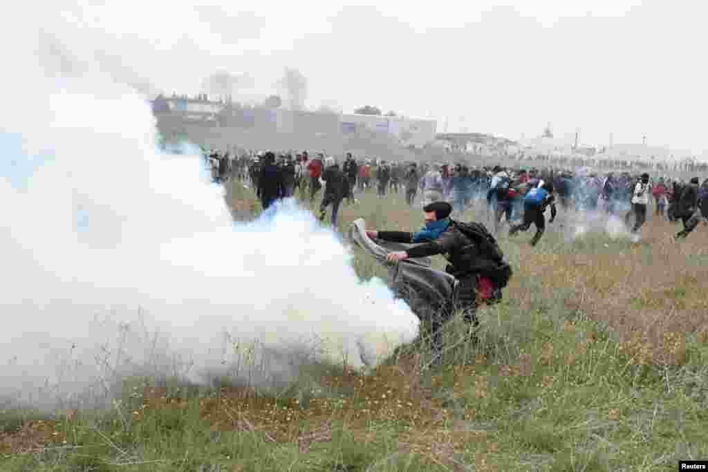 Біженець намагається прикрити ковдрою димову шашку