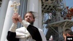 """Православ діні қызметкері """"КазCат"""" спутнигінің """"жолын ашып"""" жатыр. Байқоңыр, 17 маусым 2006 жыл."""