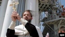 """Православный священник благославляет запуск спутника """"КазCат"""" на космодроме """"Байконур"""". 17 июня 2006 года."""