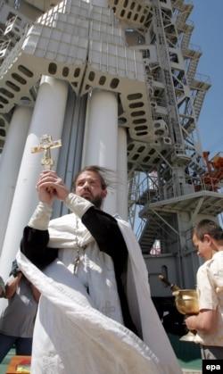 """Православный священник благословляет запуск спутника """"КазСат-1"""" на космодроме Байконур, 17 июня 2006 года."""