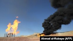 Flammable gases burn from flares at the Havana oil field, west of the northern Iraqi city of Kirkuk, on October 17.