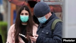 Armenia -- People wear face masks at a bus stop in Yerevan, March 17, 2020.