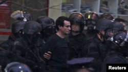 Полицейские ведут задержанного оппозиционного политика и члена парламента Косово Албина Курти. Приштина, 28 ноября 2015 года.