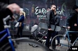 "Люди проходят мимо плаката с рекламой ""Евровидения"". Копенгаген, 3 мая 2014 года."