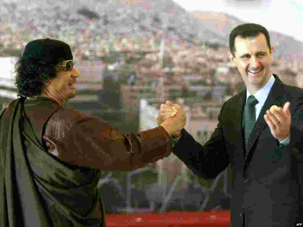 Syrian President Bashar al-Assad, who has dealt with his own antigovernment protests with a violent crackdown, clasps hands with Qaddafi at the opening session of the Arab Summit in Damascus on March 29, 2008.