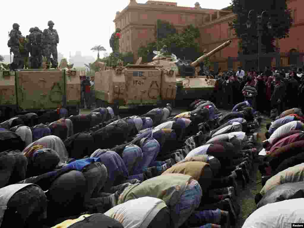 Protesters pray next to military personnel standing atop their vehicles in Cairo on January 29.