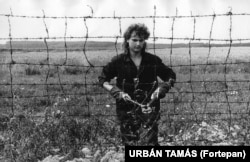 A man snips away at the border fence between Austria and Hungary in 1989. In April of that year the electric fence along the border was switched off. Parts of the barrier were later removed and the Iron Curtain separating Western Europe from communist Eastern Europe began to break down.